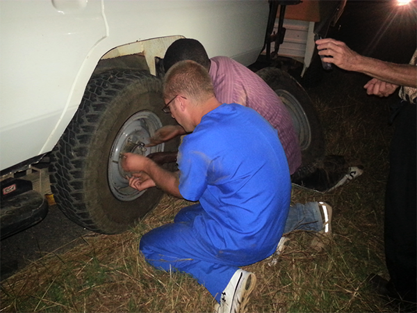 men changing tire on a truck