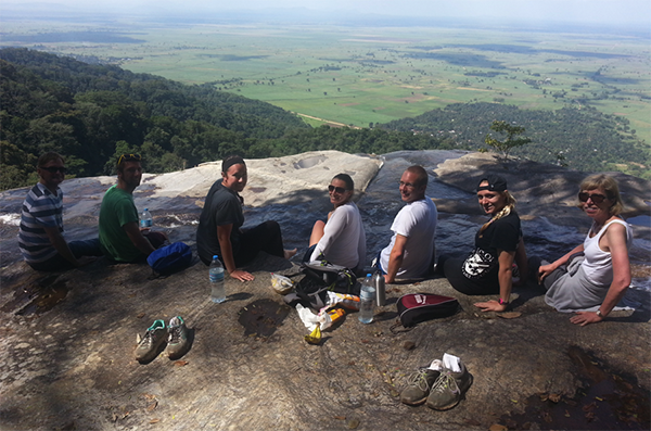Students resting on rock during hike up Sanje Falls in Tanzania